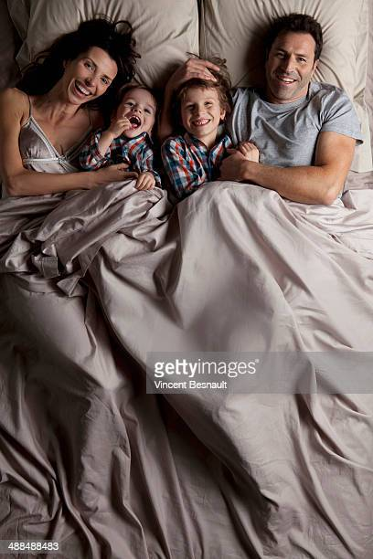 A happy family lying in a bed
