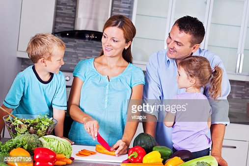 Happy family making dinner together in the kitchen : Stock Photo