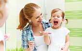 happy family mother and child little girl cleans teeth with a toothbrush in the bathroom