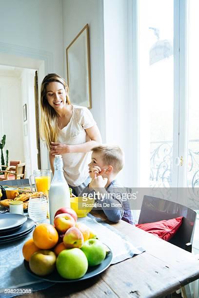 Famille heureuse, mère et fils, prenant le petit déjeuner ensemble à la maison