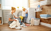 Happy family mother  housewife and children in the laundry load a washing machine