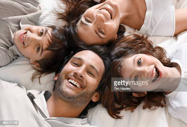 Happy family of 4 smiling at camera