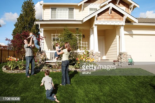 A happy family of five playing in the front yard