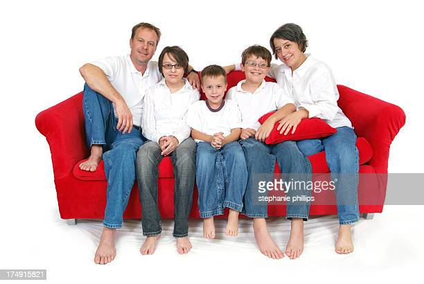 Happy Family of Five Sitting on a Big Red Couch