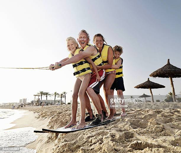 Happy family of four on water skis.