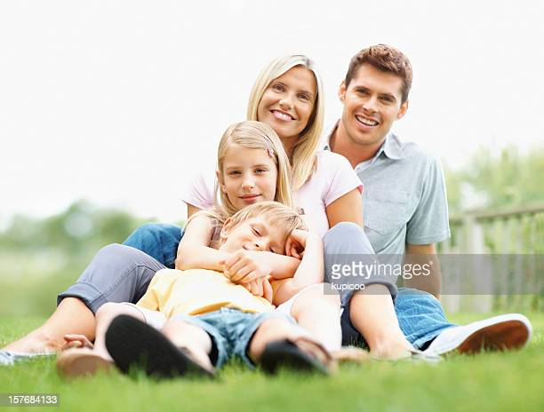 Happy family of four relaxing together on grass