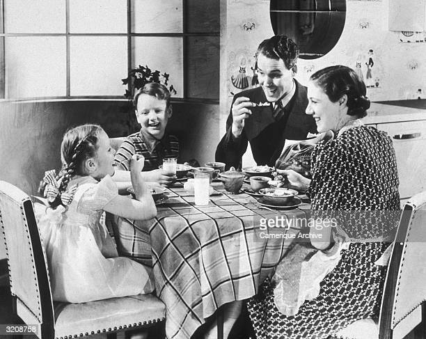 A happy family of four sits at their kitchen table while eating breakfast