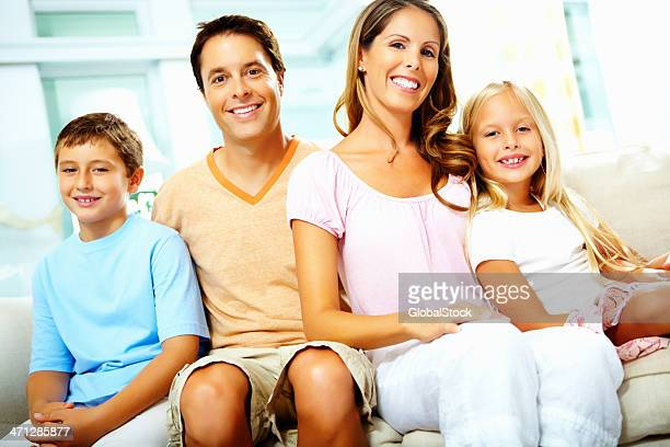 Happy family of four sitting together on sofa
