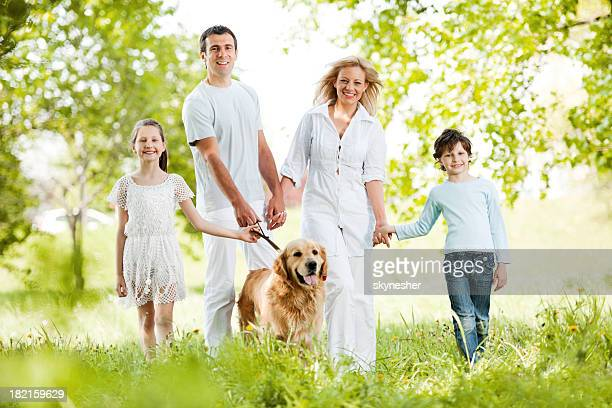 Happy family of four walking their dog in the park.