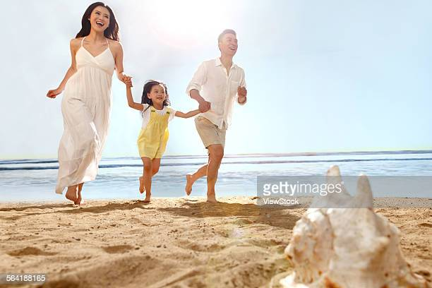 A happy family of three in the beach hand in hand to run