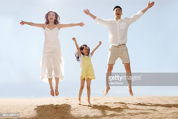 A happy family of three in the sea jump