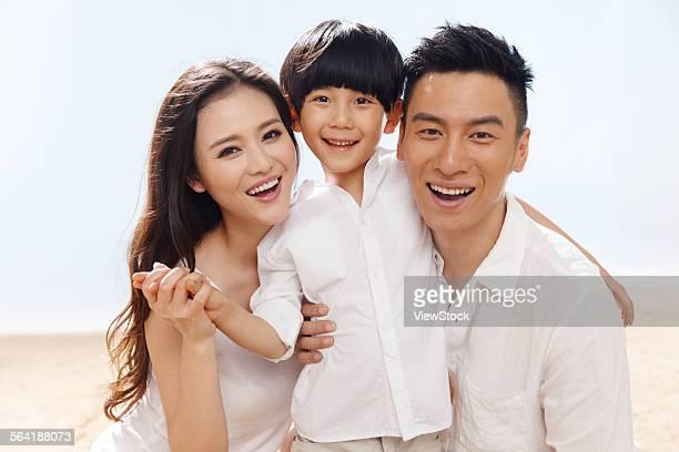 A happy family of three on the beach