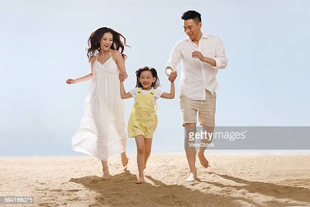 A happy family of three playing on the beach