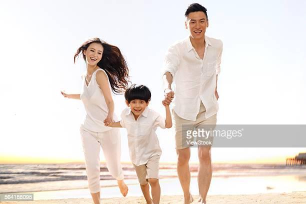 A happy family of three ran on the beach