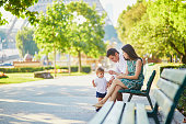 Happy family of three sitting on the bench in park near the Eiffel tower and enjoying their vacation in Paris, France