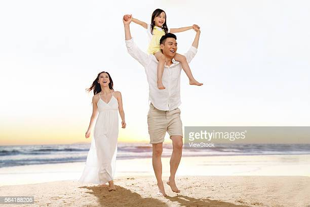 A happy family of three to take a walk in the seaside