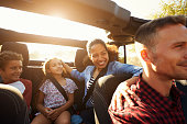 Happy family on a road trip in car, front passenger POV