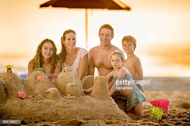 Happy family on vacation building a sand castle
