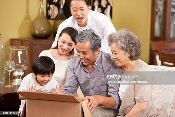 Happy family opening a carton with surprise