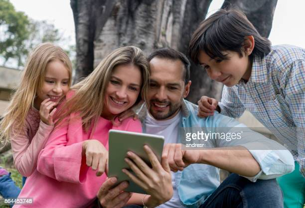 Happy family outdoors looking at a tablet computer