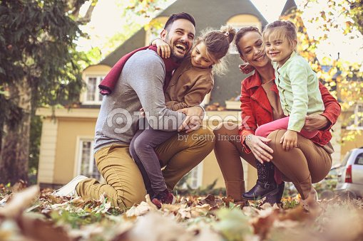 happy family outside in colorful fall backyard poses to camera stock