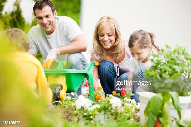 Happy family planting flowers.