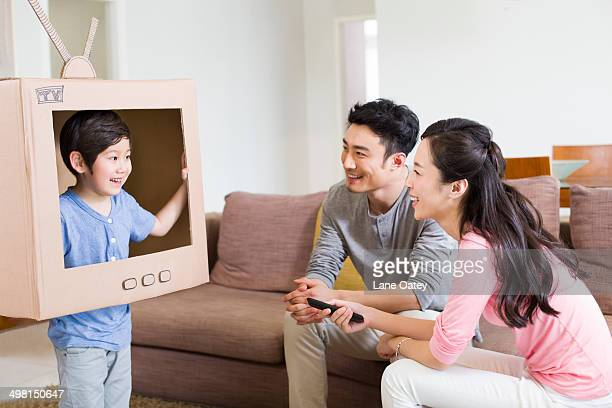Happy family playing cardboard television