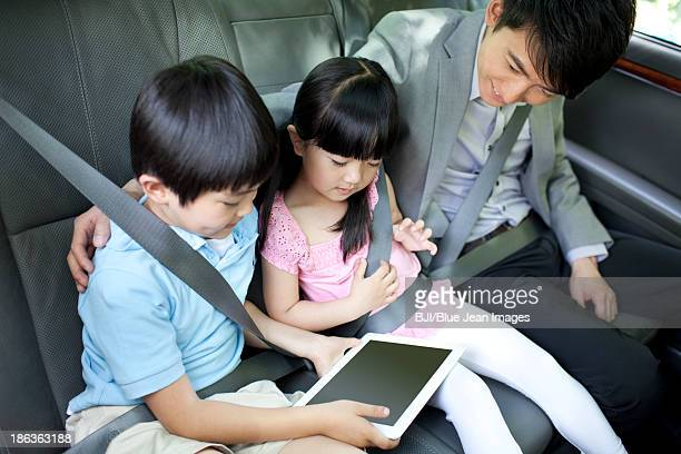 Happy family playing digital tablet in car