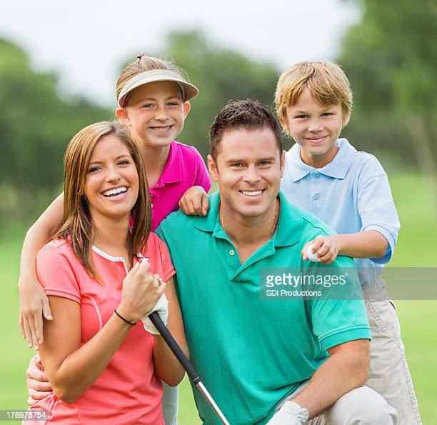 Happy family playing golf together on green course