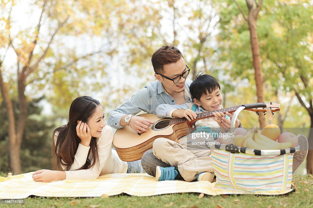 happy family playing guitar in park : Stock Photo