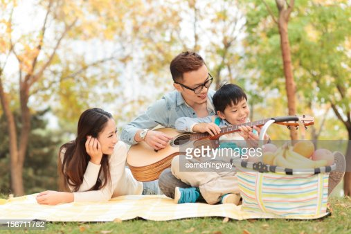 happy family playing guitar in park : Foto de stock