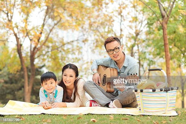 happy family playing guitar in park