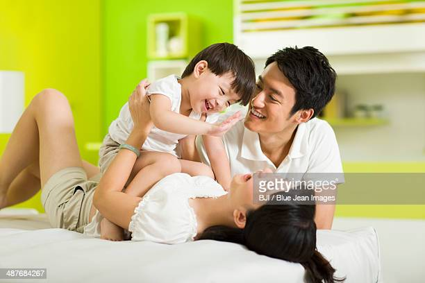 Happy family playing in bedroom