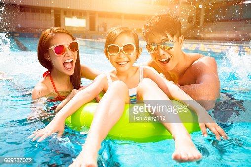 Familia feliz jugando en la piscina : Foto de stock