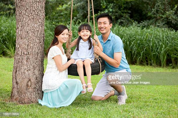 Happy family playing on a swing outdoors