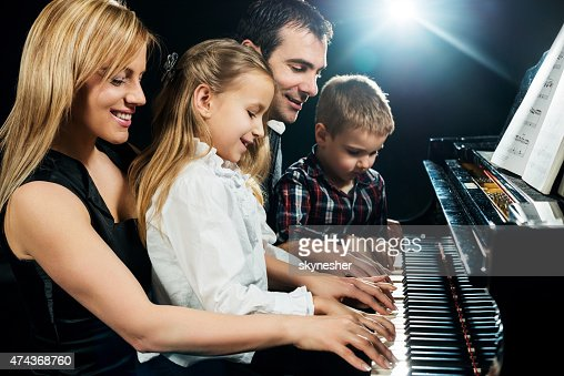 Happy family playing piano together.