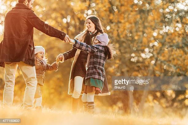 Felice famiglia giocando anello attorno al rosee in autunno.