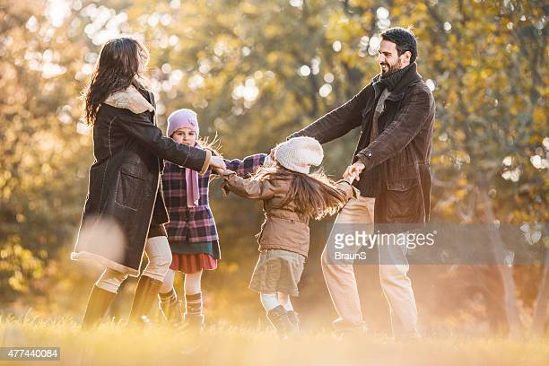 Happy family playing ring around the rosy in autumn.
