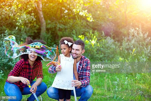 Família feliz de jogar bolhas de sabão no parque.