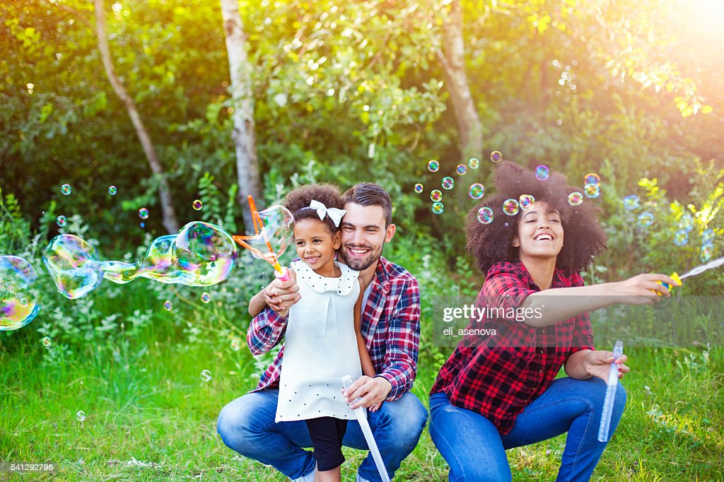 Happy family playing soap bubbles in park. : Stock Photo