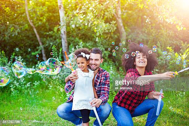 Happy family playing soap bubbles in park.