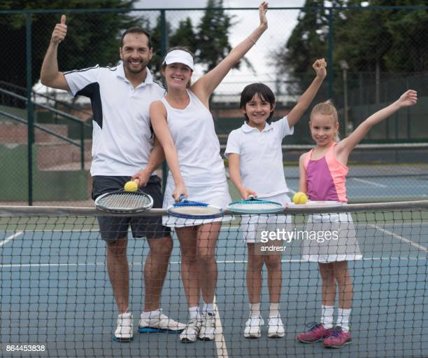 Happy family playing tennis outdoors