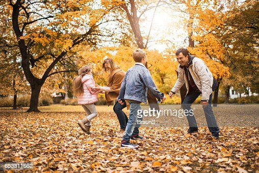 Happy family playing together in autumn day. : Bildbanksbilder