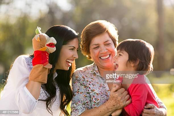 Glückliche Familie spielen mit einer Puppe