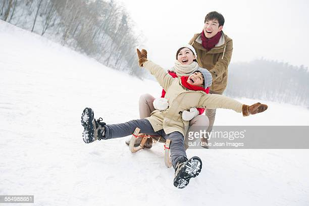 Happy family playing with sled on the snow