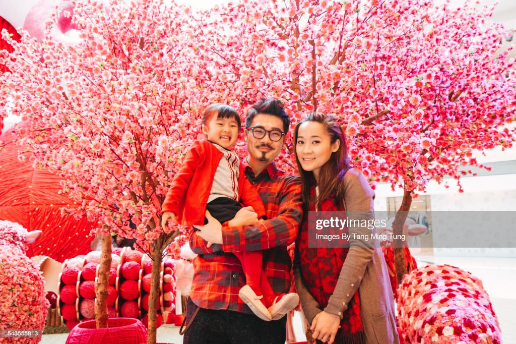 A happy family portrait in front of CNY decoration