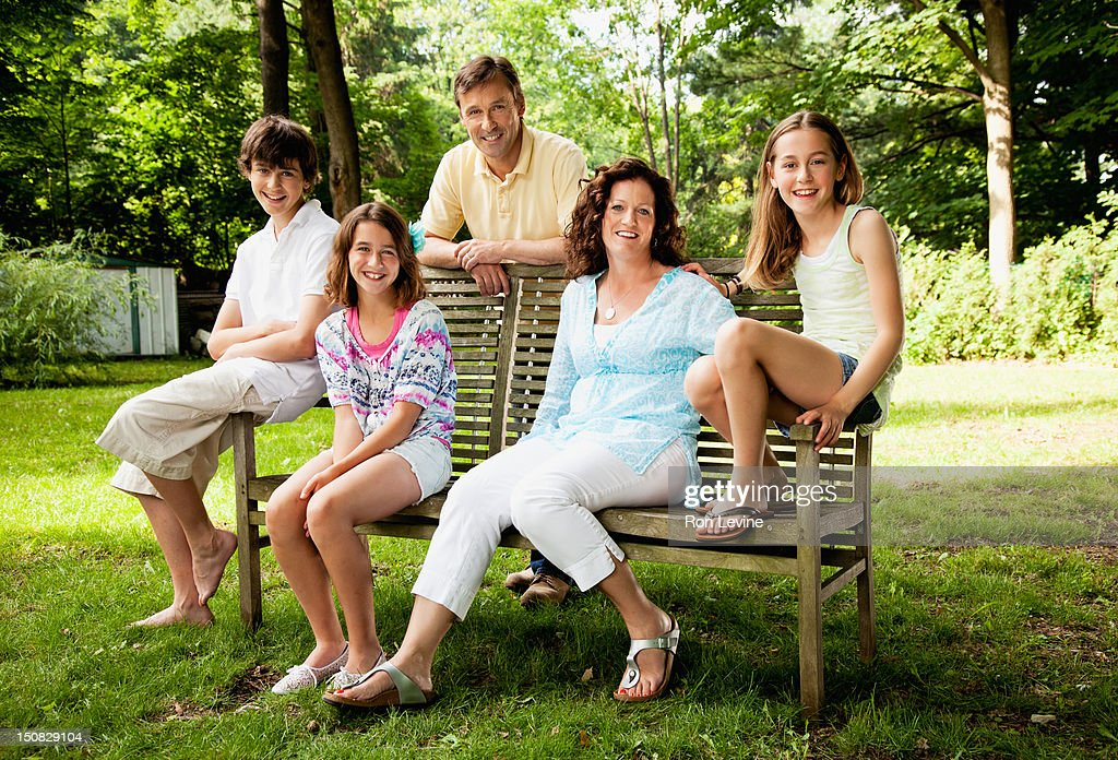 Happy family portrait on a park bench : Stock Photo