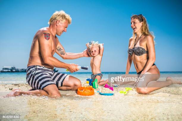 Happy family portrait: young couple with kid on vacation. Clear blue sky, azure water, happiness