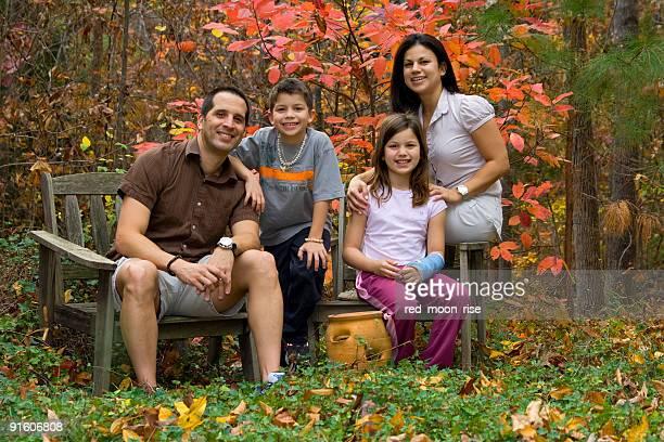 Happy family posing in a fall garden landscape