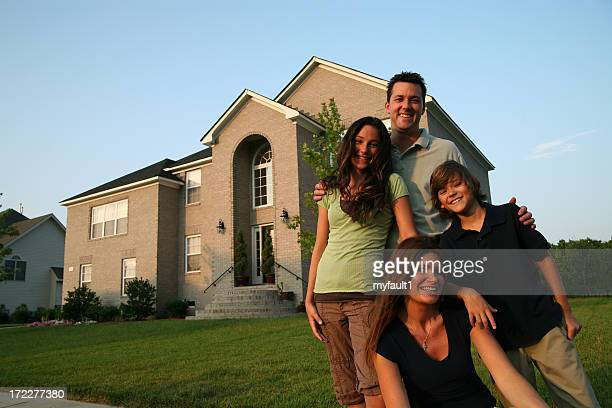 Happy family posing in front of a house